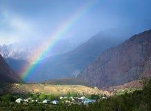 Arco iris sobre el pueblo en las montañas Paisaje entonado Fotos de archivo