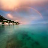 Arco iris sobre Rocky Beach y pequeño pueblo después de la lluvia Foto de archivo