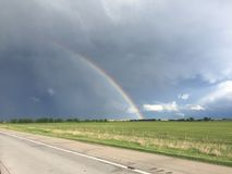 Arco iris sobre un camino del campo del camino y de hierba con los cielos nublados Fotografía de archivo libre de regalías