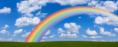 Arco iris a través del campo verde Foto de archivo