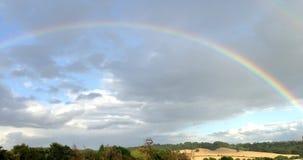 Arco iris a través del cielo azul sobre las colinas verdes Fotografía de archivo libre de regalías