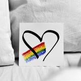 Arco iris y corazón en una nota fotografía de archivo libre de regalías