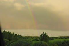 Arco iris y nubes y bosque en puesta del sol Imagen de archivo