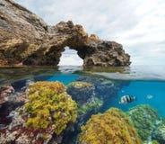 Arco naturale di formazione rocciosa con le alghe ed il pesce subacquei fotografie stock
