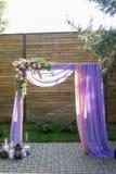 Arco púrpura de la boda adornado con las flores, la lila y el material rosado La plataforma hermosa para una ceremonia de boda de Imagen de archivo