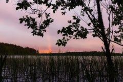 Arco-?ris sobre o lago no por do sol imagem de stock