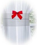 Arco rojo de Chrismas en la cortina blanca con el cristal de ventana y el tre nevoso Fotos de archivo libres de regalías
