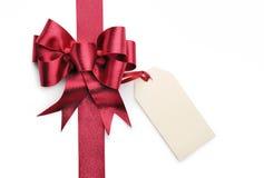 Arco rojo de la cinta con la etiqueta en blanco del regalo Imagenes de archivo