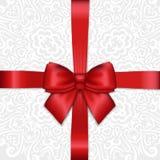 Arco rojo de la cinta de satén del día de fiesta brillante en el CCB de encaje blanco del ornamental Fotos de archivo libres de regalías