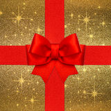 Arco rojo de la cinta sobre fondo de oro Imagen de archivo libre de regalías