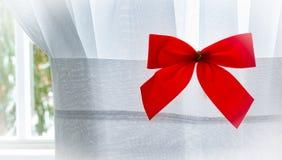 Arco rojo de la Navidad en la cortina blanca interior con los árboles nevosos afuera Foto de archivo