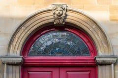 Arco rosso della porta con la scultura trapezoidale del bambino Immagini Stock