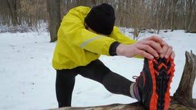Arco tirado del hombre apto atlético que estira las piernas antes de correr en bosque del invierno metrajes