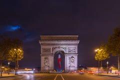 Arco trionfale di Parigi Arc de Triomphe alle screpolature Elysees alla notte, Immagini Stock
