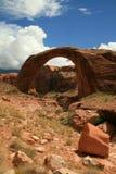 Arco vermelho de encontro a um céu azul e a umas nuvens brancas Fotos de Stock Royalty Free