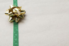 Arco y cinta envueltos regalo en el papel reciclado Fotos de archivo