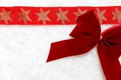 Arco y cinta rojos con las estrellas en la nieve, fondo festivo Foto de archivo libre de regalías