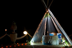 Arco y disposición de la boda con las flores en la playa en la noche Imagenes de archivo
