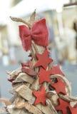arco y estrellas rojos encima de un árbol de navidad de madera Imagen de archivo