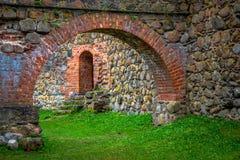 Arco y pared de piedra en patio interno imagenes de archivo