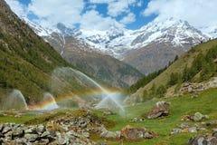 Arcobaleni in becchi di acqua di irrigazione in montagna delle alpi di estate Fotografia Stock Libera da Diritti