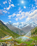 Arcobaleni in becchi di acqua di irrigazione in montagna delle alpi di estate Fotografia Stock