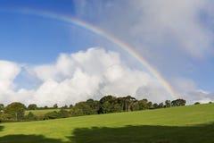 arcobaleno ad alba sopra i campi con cielo blu Fotografia Stock