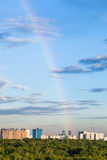 Arcobaleno in cielo blu di sera sopra i condomini Immagini Stock