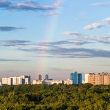Arcobaleno in cielo blu sopra le case moderne Immagine Stock