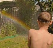 Arcobaleno del tubo flessibile del ragazzo nel giardino Immagine Stock Libera da Diritti