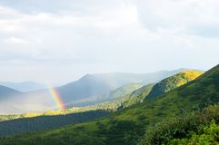 Arcobaleno e luce solare nelle montagne sopra le case Fotografie Stock