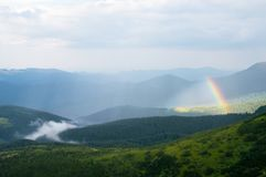 Arcobaleno e nebbia nelle montagne sopra le case Fotografie Stock