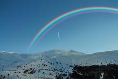 Arcobaleno nelle montagne nevose Fotografia Stock Libera da Diritti