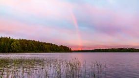 Arcobaleno sopra il lago al tramonto immagini stock