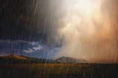Arcobaleno sopra il paesaggio della montagna con le nuvole pesanti Fotografia Stock