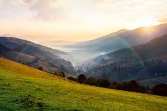 Arcobaleno sopra il villaggio in valle nebbiosa Fotografie Stock Libere da Diritti