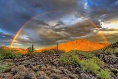 Arcobaleno sopra la montagna nera Fotografia Stock