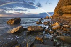 Arcobaleno sopra la scogliera dopo avere passato una tempesta di sera Immagine Stock