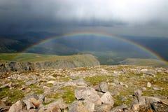 Arcobaleno sopra la valle della montagna Immagini Stock