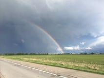 Arcobaleno sopra una strada del giacimento di erba e della strada con i cieli nuvolosi Fotografia Stock Libera da Diritti