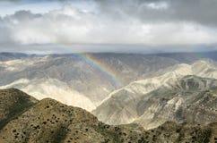 Arcobaleno variopinto nelle montagne nepalesi dopo i rai distanti Immagini Stock