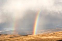 Arcos-íris acima do campo de trigo nas montanhas Fotografia de Stock Royalty Free