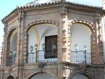 Arcos con las verjas y las pequeñas lámparas en un edificio central en Antequera en España Foto de archivo