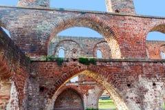 Arcos del ladrillo rojo en una ruina de un edificio del monasterio, septentrional Foto de archivo