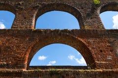 Arcos vacíos de la ventana y cielo azul en la pared de ladrillo del monast Foto de archivo