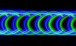 Arcs red luminous beads accented by green and blue lights. Multi-colored light lines painted the darkness in green, blue and their shades. There are a Royalty Free Stock Photography