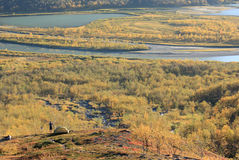 Arctic autumn. Man taking photo of Arctic scenery in autumn colors from a cool campsite in the mountains Royalty Free Stock Image