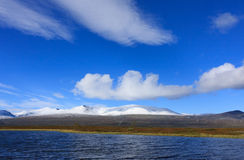 Arctic autumn view. Lake in the arctic wilderness with snow capped mountains Stock Photos