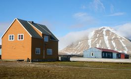 Arctic buildings. Two buildings set against a backdrop of a mountain.  This part of the research center in Ny Alesund in the Svalbard region of the Arctic Stock Image