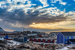 Arctic houses growing on the rocky hills in sunset panorama. Nuu Stock Image